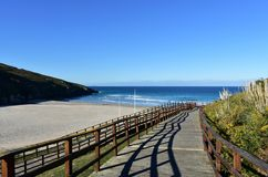 Beach with wooden boardwalk, vegetation, golden sand and blue sea with small waves. Morning light, sunny day, Galicia, Spain. Arteijo, La Coruna province royalty free stock photography