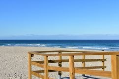 Beach with wooden handrail and morning light. Golden sand and blue sea with waves and white foam. Sunny day, Galicia, Spain. Arteijo, La Coruna Province royalty free stock image