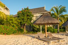 Beach with wooden parasol garden and bungalow. Beach at Mauritius island with wooden parasol,garden and bungalow, sunny day Royalty Free Stock Images