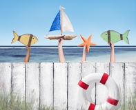 Beach and Wooden Plank Fence with Hands Holding Toys Royalty Free Stock Photos