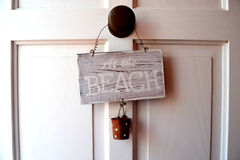 At the beach. Wooden sign with the message at the beach in white door, illuminated with natural light Stock Photo
