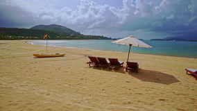 Beach with wooden tables chairs chaise-longues boat by wave surf stock video
