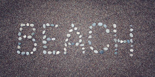 'Beach' word on the sand. Written with pebbles. Aged photo. Royalty Free Stock Photo
