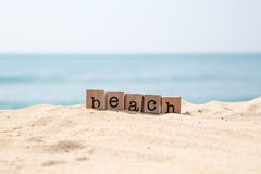Beach word on seaside with blue ocean background Royalty Free Stock Photography