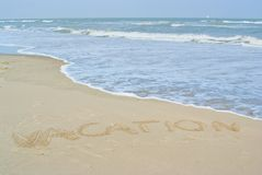 Beach and the word vacation written in the sand Royalty Free Stock Photo