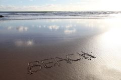 Beach word written in sand. BEACH written in the sand with the sea behind. Ideal for beach holiday promotions Stock Photos