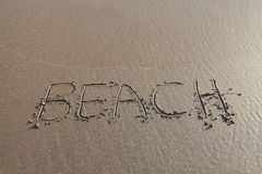 Beach word written in sand. BEACH written in the sand with the sea behind. Ideal for beach holiday promotions Stock Image
