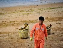Beach worker, Qingdao, China. Worker on the beach at the seaside coastal town of Qingdao 青岛· known for it`s beautiful beaches and year round warm weather Royalty Free Stock Photos