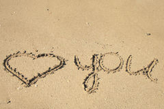 Beach writing. Love message written on the sand Stock Images