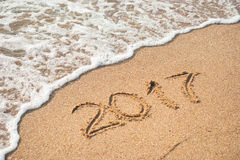 2017 on the beach 3. 2017 written on empty wet yellow beach sand washed by sea wave stock photos
