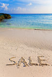 On a beach it is written SALE Stock Image
