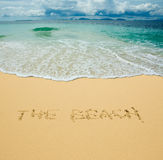 The beach written in a sandy tropical beach Stock Image