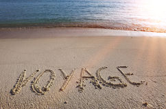 On a beach it is written voyage.  Stock Photos
