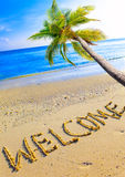 On a beach it is written Welcome and a palm tree Stock Images