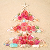Beach Xmas concept on sand as a Christmas tree with shells and f Stock Photos