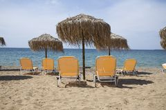 Beach with yellow chairs Stock Image