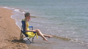 Beach, yellow dress, blue chair Royalty Free Stock Photo
