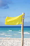 Beach yellow flag. Warning weather wind at Cuban turquoise sea Royalty Free Stock Photos