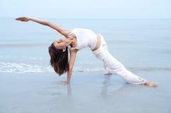 Beach Yoga. Woman practising Yoga(Gate Pose) on the beach Stock Photography