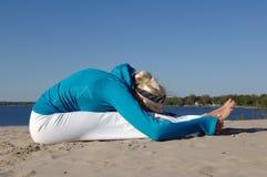 Beach yoga. Sporty looking woman practices yoga on the beach Stock Photos