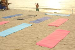 Beach yoga lesson preparation with mat on sand and sea background stock images