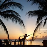 Beach yoga during sunset. With palm trees in Royalty Free Stock Photos