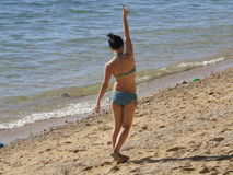 On the Beach. Young adult girl in a bikini walking away on a beach with arm extended in the air, fingers forming peace sign Stock Photos