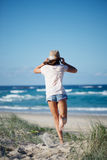 At the beach. Young girl running towards the ocean on the green grass dune of a beautiful white sand beach in Australia Royalty Free Stock Image