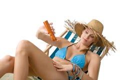 Beach - Young woman apply suntan lotion Stock Photos