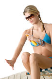 Beach - Young woman in bikini apply suntan lotion Royalty Free Stock Photo