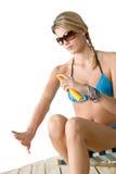 Beach - Young woman in bikini apply suntan lotion Royalty Free Stock Photo