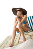 Beach - Young woman in bikini sit on deck chair. Beach - Young woman in bikini sitting on deck chair relaxing wearing big hat and sunglasses Stock Photography