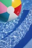 Beachball in einem schönen blauen Swimmingpool Lizenzfreie Stockfotografie