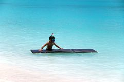 Beachboy. Little boy snorkeling with air mattress in the turquoise indian ocean Stock Photography