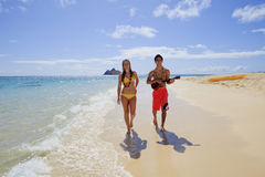 Beachboy plays his ukulele for a girl Royalty Free Stock Image