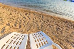 2 beachchairs на песке около моря, крупного плана Стоковая Фотография RF