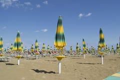 Beache-Regenschirme mit Strandstühlen am Ende der Sommersaison Stockbild