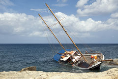 Beached. Schooner shipwrecked and beached on coastline rocks stock image