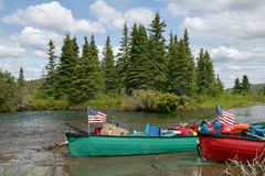 Beached American canoes on Alaskan river bank. Two beached canoes with American flags on a remote, scenic Alaskan river bank with a sunny blue sky and lush stock image