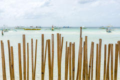 A Beached Bamboo fence. Looking through a bamboo pole barrier fence in a tropical island white sand beach out to a calm crystal clear sea with pump boats royalty free stock photos