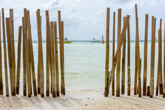A Beached Bamboo fence. Looking through a bamboo pole barrier fence in a tropical island white sand beach out to a calm crystal clear sea with pump boats stock photo