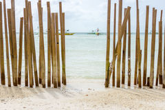 A Beached Bamboo fence. Looking through a bamboo pole barrier fence in a tropical island white sand beach out to a calm crystal clear sea with pump boats stock photography