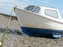Beached Boat. Small motorboat lying beached in mud, secured by a weed covered cable. Rock in background Royalty Free Stock Photos