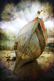 Beached boat. Abstract textured image of a beached fishing trawler to give a well worn vintage look stock photo