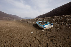 Beached boat. At a lake on cracked soil during a  drought Royalty Free Stock Images