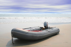 Beached boat. Beached inflatable boat with ocean waves in background royalty free stock images
