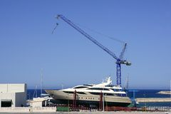 Beached boat with crane on storage area. Luxury yacht Stock Images