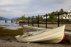 Beached Boat on Kyleakin. A small beached fishing boat rests upon the docks near the loche surrounding the small island town of Kyleakin. Castle ruins can be Royalty Free Stock Photography