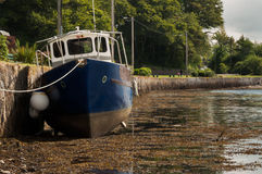 Beached boat at low tide. Low tide at Kenmare harbour Stock Image