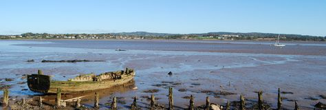 Beached boat. Old rotting rowing boat at low tide at Exmouth Bay Stock Photo